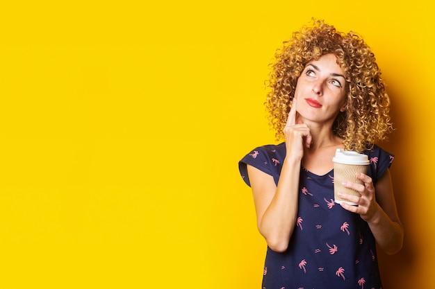 Nadenkend jonge vrouw met krullend haar met een kartonnen beker op een gele ondergrond