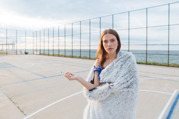 Nadenkend jonge vrouw met lang haar denken en sigaret roken op de playgroud