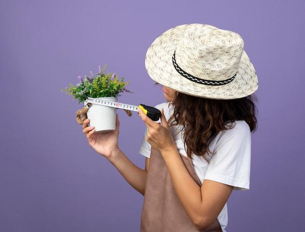 Nadenkend jonge vrouwelijke tuinman in uniform dragen tuinieren hoed meten bloem in bloempot met meetlint geïsoleerd op paars