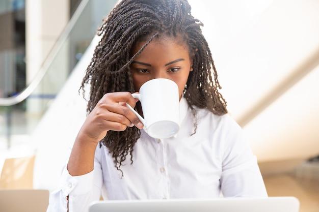 Nadenkend jonge vrouwelijke werknemer koffie drinken