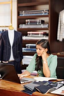 Nadenkend jonge zakenvrouw bezig met laptop in atelier, stoffen en benodigdheden bestellen en e-mails beantwoorden