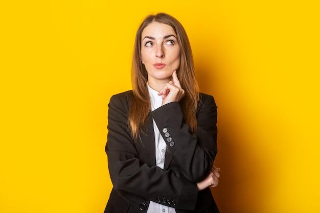 Nadenkend jonge zakenvrouw dame in zwarte jas opgezocht op geel.