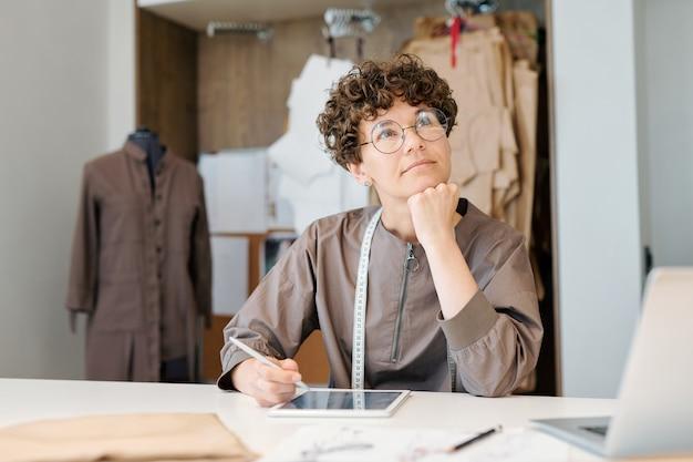 Nadenkend jongedame denken aan nieuwe ideeën tijdens het werken over mannequins door bureau in werkplaats