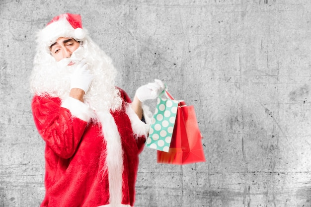 Nadenkend kerstman bedrijf boodschappentassen