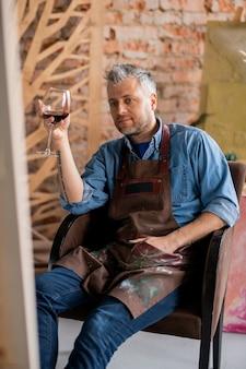 Nadenkend kunstenaar met glas rode wijn kijken naar zijn schilderij op ezel zittend in een stoel na het beëindigen van het werk