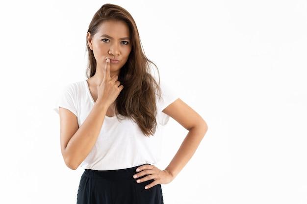 Nadenkend lachende jonge vrouw aanraken van de lippen