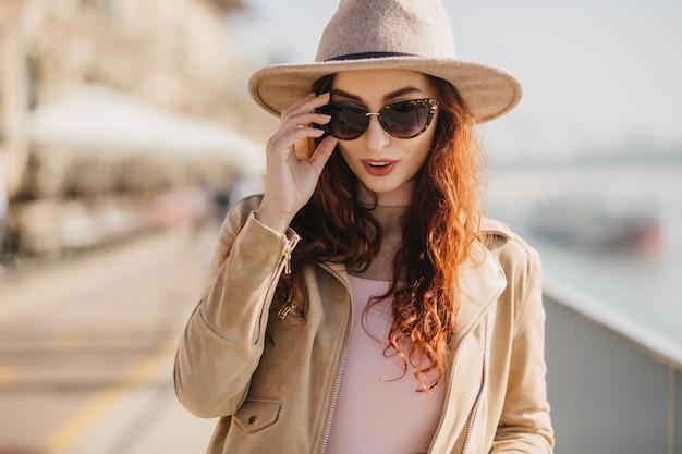 Nadenkend langharige vrouw haar zonnebril aanraken tijdens het lopen op de kade