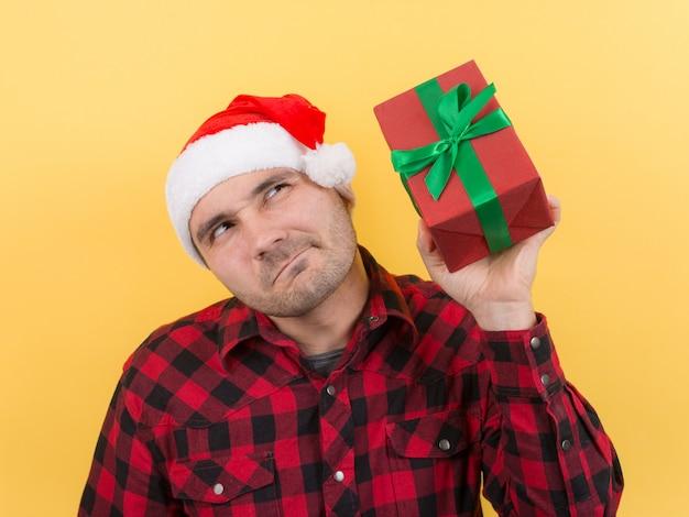 Nadenkend man in een rode hoed, houdt een geschenk met belangstelling op zijn gezicht