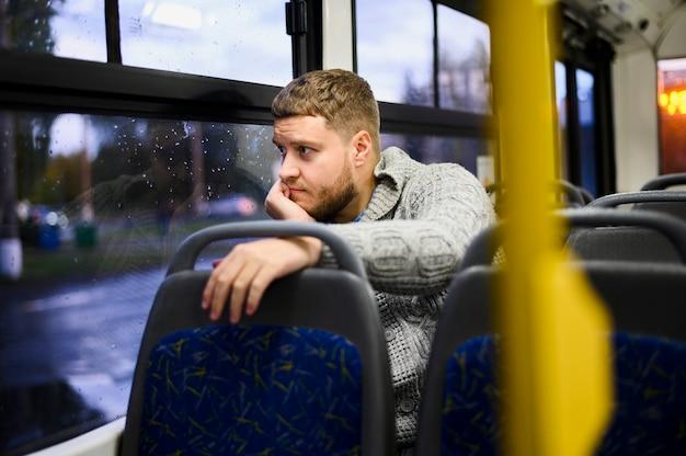 Nadenkend man kijkt uit het raam van de bus