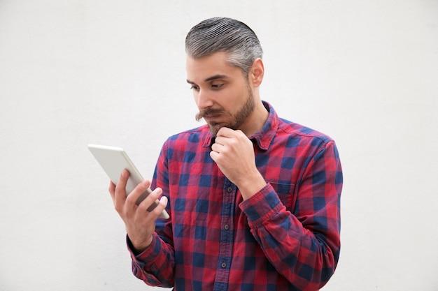 Nadenkend man met hand op kin met behulp van tablet pc