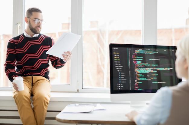 Nadenkend manager leesrapport aan programmeur
