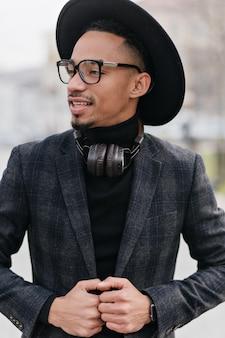 Nadenkend mannelijk model met donkere huid wegkijken tijdens buiten fotoshoot. prachtige afrikaanse jonge man in vintage hoed poseren