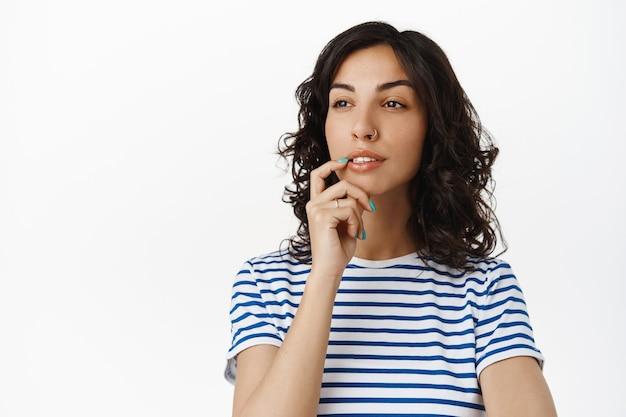 Nadenkend meisje dat opzij kijkt en een keuze maakt, raak de lip nadenkend aan, denkend, staande op wit in gestreept t-shirt
