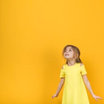 Nadenkend meisje in gele kleding