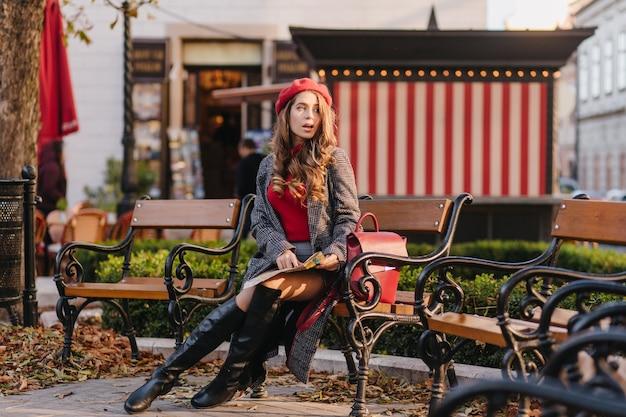 Nadenkend meisje in knie hoge laarzen zittend op een bankje en wegkijken met open mond