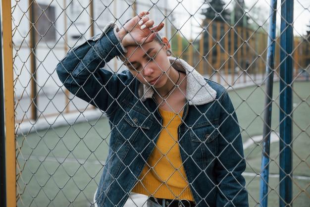 Nadenkend meisje in vrijetijdskleding, leunend op het hek buitenshuis