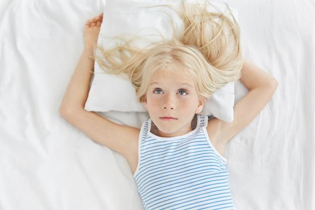 Nadenkend meisje met lang blond haar dat omhoog kijkt, gestreept overhemd draagt, liggend op wit hoofdkussen, droomend over nieuwe fiets. rustgevend aanbiddelijk meisje dat op wit bed in kinderen` s ruimte rust