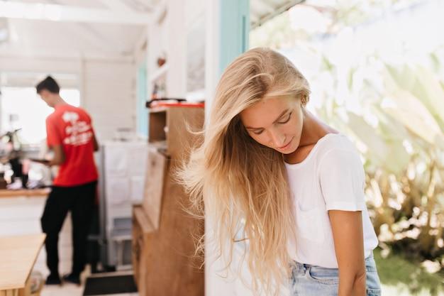 Nadenkend meisje met lang licht haar poseren thuis. binnen schot van dromerig wit vrouwelijk model in trendy t-shirt naar beneden te kijken terwijl je in cafetaria staat.