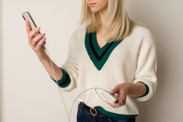 Nadenkend meisje speelt in de telefoon en infecteert deze via een powerbank. powerbank in handen van het meisje. powerbank gebruiken en games spelen.