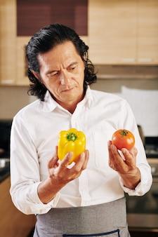 Nadenkend mens die groenten bekijkt