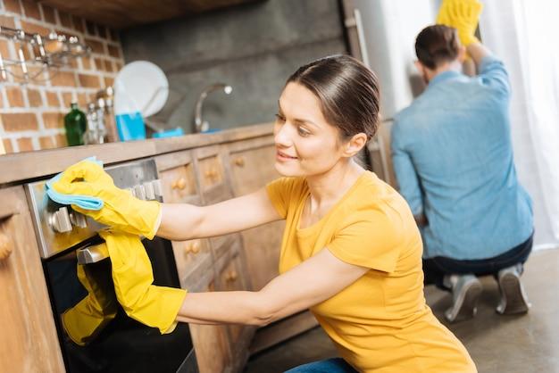 Nadenkend mijmerend verheugde de vrouw de oven te polijsten terwijl ze ernaar keek en haar echtgenoot hielp