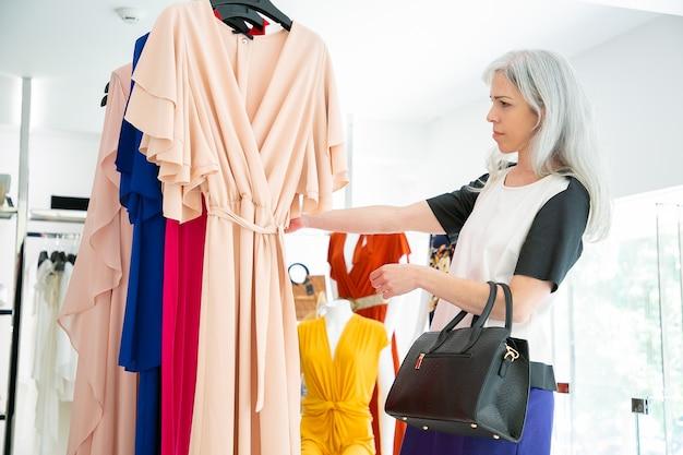 Nadenkend mode winkel klant kleding kiezen en jurken op rek browsen. medium shot, zijaanzicht. modewinkel of winkelconcept