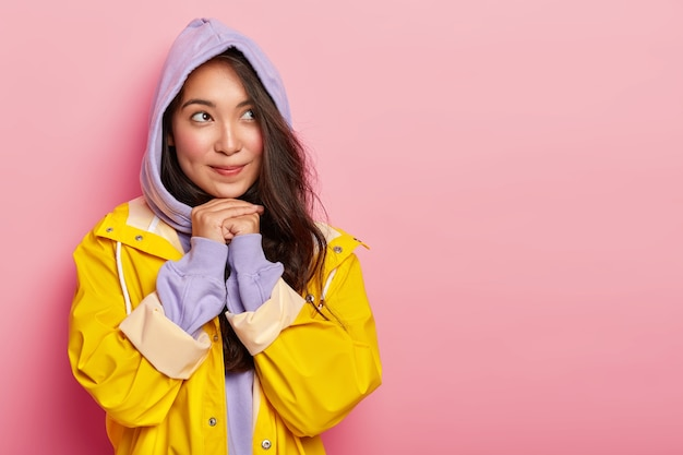 Nadenkend mooi brunette koreaans meisje houdt de handen bij elkaar onder de kin, kijkt opzij, draagt een paarse capuchon op het hoofd