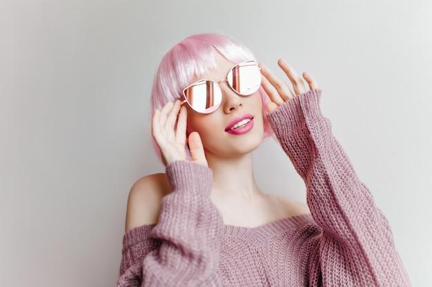 Nadenkend mooi meisje die in roze periwig omhoog op lichte muur kijken. indoor foto van kortharige stijlvolle vrouw in paarse gebreide kleding en peruke.