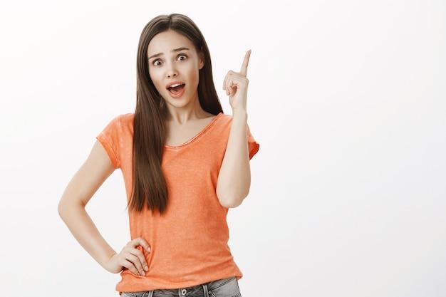 Nadenkend mooi meisje heeft een idee, steekt de vinger op, onthoud iets, bedenk een oplossing