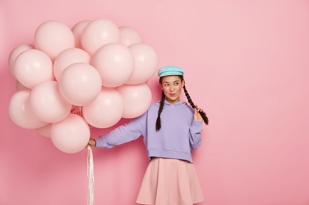 Nadenkend mooi meisje met rode wangen, gekleed in modieuze kleding, houdt een heleboel ballonnen vast, komt op feestje