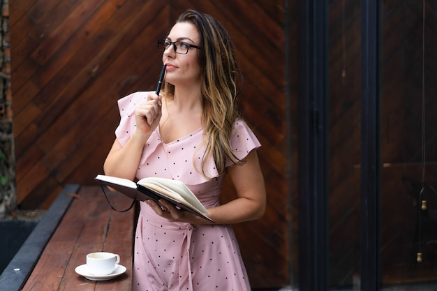Nadenkend mooi notitieboekje van de vrouwenholding in koffie