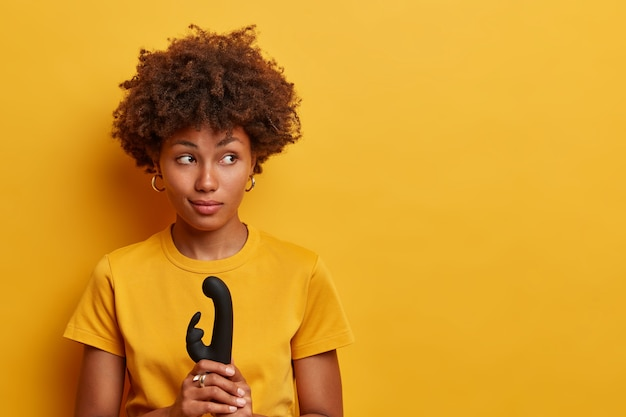 Nadenkend mooie vrouw met afro-haar gaat de vibrerende kracht van nieuw seksspeeltje verkennen, houdt vibrator vast voor de vagina, stimulatie van de clitoris, gebruikt stimulator op verschillende delen van het lichaam, bereikt een orgasme