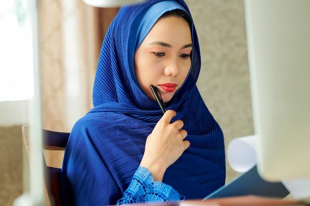 Nadenkend moslimvrouw leesdocument