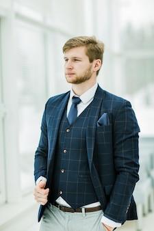 Nadenkend nieuwkomer zakenman in een pak staat in de buurt van een raam