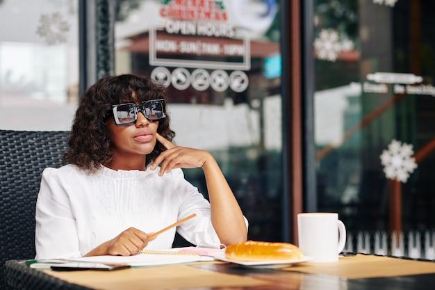 Nadenkend onderneemster aan koffietafel