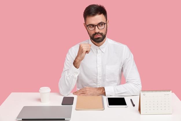 Nadenkend, ongeschoren man die opzij is gericht met een bedachtzame uitdrukking, draagt een elegant wit overhemd, denkt na over het ontwikkelen van zaken