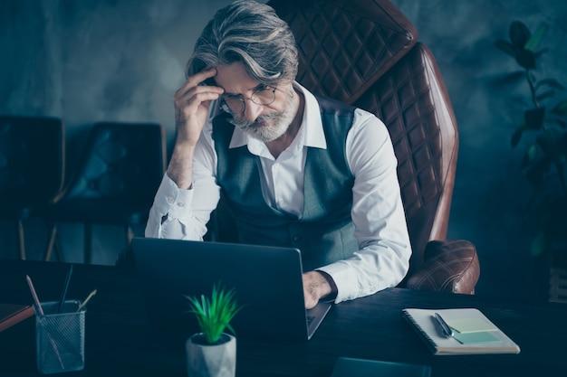 Nadenkend oude man advocaat zitten tafel werk op laptop in kantoor