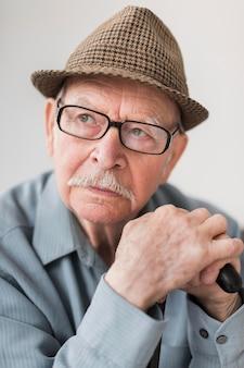 Nadenkend oude man met bril en stok