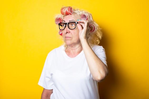 Nadenkend oude vrouw met krulspelden in glazen kijkt naar de zijkant op een geel oppervlak