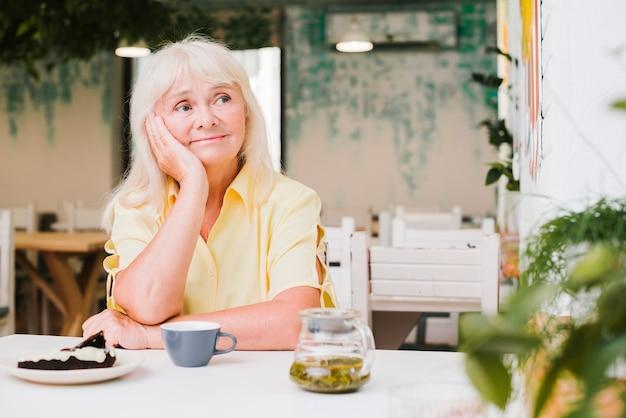 Nadenkend oudere vrouw zitten aan tafel in café