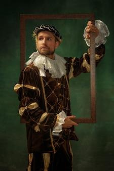 Nadenkend poseren. portret van middeleeuwse jonge man in vintage kleding met houten frame op donkere achtergrond. mannelijk model als hertog, prins, koninklijk persoon. concept vergelijking van moderne tijdperken, mode.