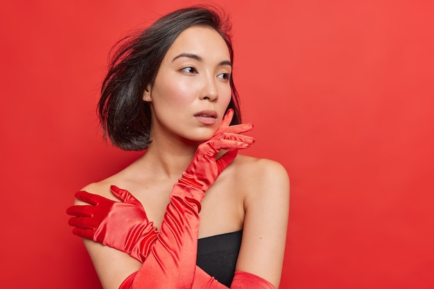 Nadenkend prachtige aziatische dame draagt zwarte jurk lange handschoenen jurken voor speciale gelegenheid kijkt bedachtzaam weg heeft donker haar zwevend in de lucht geïsoleerd over levendige rode muur