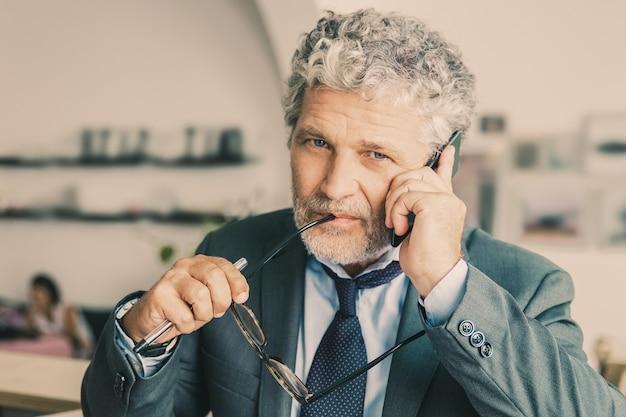 Nadenkend rijpe zakenman die op mobiele telefoon spreekt, die zich bij co-working bevindt, leunend op bureau