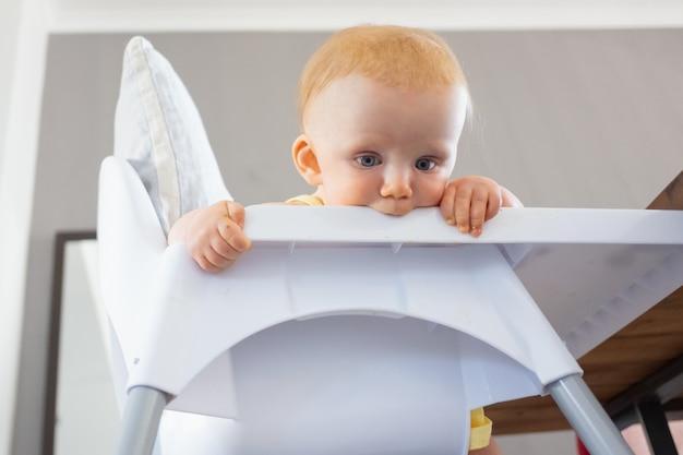 Nadenkend roodharige baby die neer op vloer van hoge stoel en dienblad bijten. lage hoek. voedingsproces of kinderopvangconcept
