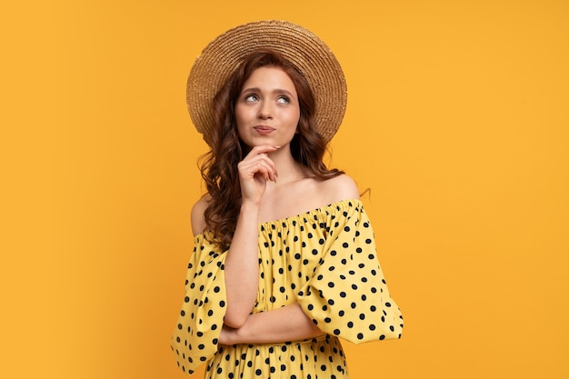 Nadenkend roodharige vrouw poseren in gele jurk met mouwen op geel. zomerstemming.