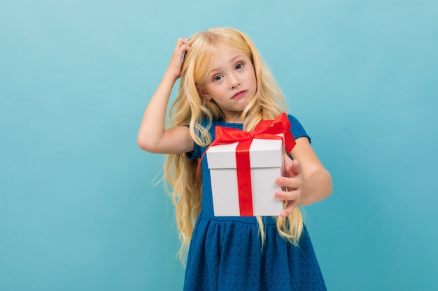 Nadenkend schattig blond meisje in een jurk met een cadeau in haar handen op een lichtblauwe achtergrond
