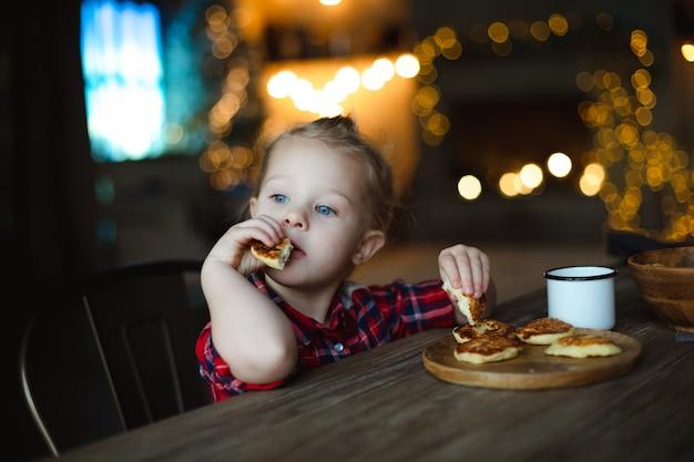 Nadenkend schattig klein meisje met ontbijt met cheesecakes.