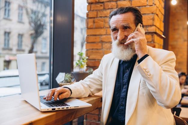 Nadenkend senior man, met een witte baard, glimlacht kijken naar zijn laptop en nemen via de telefoon. een oudere blanke persoon. oudere persoon en nieuwe technologie