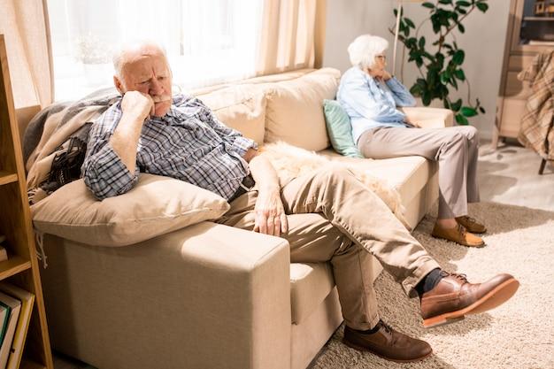 Nadenkend senior man rustend op de bank