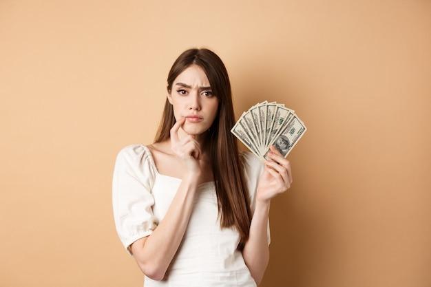 Nadenkend serieus meisje houdt geld vast en denkt, kijkt bedachtzaam naar de camera en fronst fronsen, besluit wat te kopen met dollarbiljetten, beige.